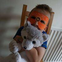 Close up of boy with homemade mask at be my bear party cuddling bear