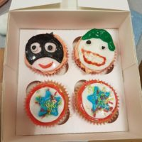 Close up of assorted superhero decorated cupcakes in white box
