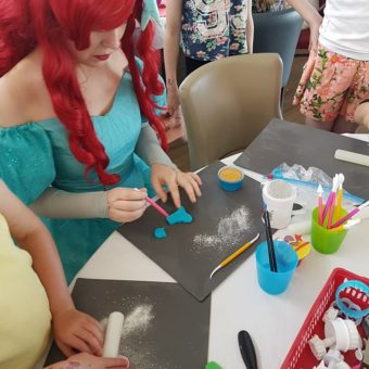 Woman dressed as Ariel from the Little Mermaid helping children with crafts at party