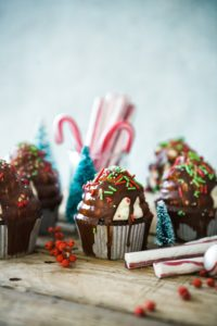 Christmas cupckaes and candy canes on wooden table