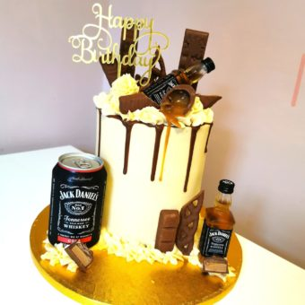 Tall cream and brown buttercream Jack Daniel's and chocolate themed birthday cake