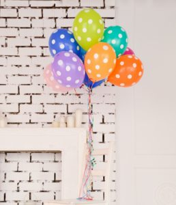 Multicoloured bunch of white spotted balloons tied to a chair on a white brick background