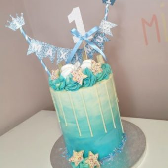"""Tall cream and blue buttercream drip 1st birthday cake for """"Maximus"""" decorated with white chocolate sprinkle stars"""
