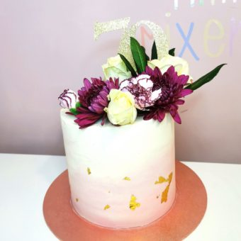 Tall pink and cream buttercream 70th birthday cake decorated with purple and cream flowers