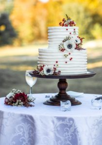 Two tier white buttercream wedding cake with ribbed pattern, white and red flowers on a table outside