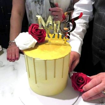 Tall buttercream cream wedding cake with gold drip, Mr & Mrs topper and white and red roses