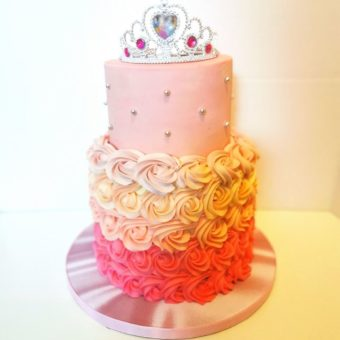 Two tier pink buttercream birthday cake bottom tier decorated with graduated pink buttercream flowers with tiara on top